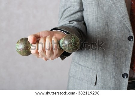 A dumbbell in the hand of a man in a classical costume. Closeup