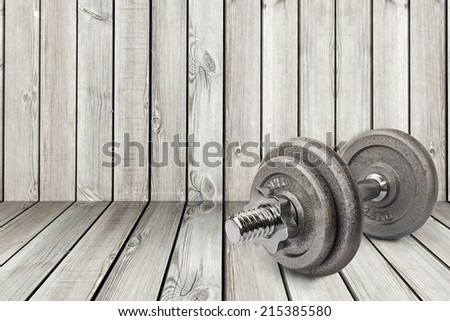 a dumbbell is on the old wood background - stock photo
