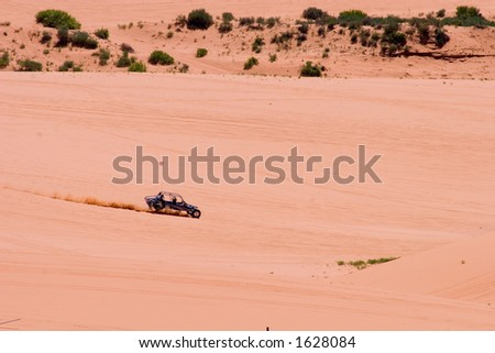 A dune buggy kicks up a wake as it crosses pink coral sands at a state park in Utah. - stock photo