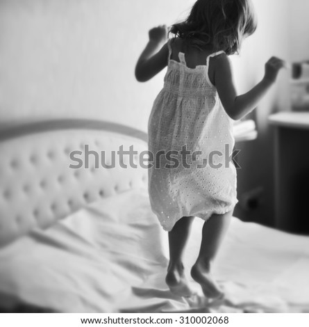 A dynamic indoor portrait of a little girl jumping on a king size bed, black and white photo - stock photo