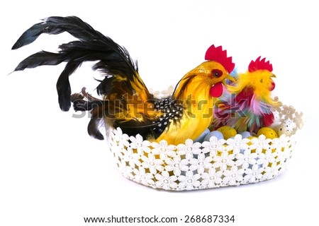 A Easter chicken and a cock in a basket with artificial eggs - stock photo