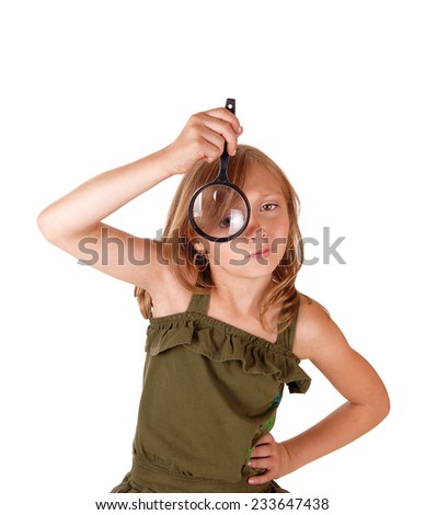 A eight year old girl holding a magnifying glass before her eye, isolated for white background.