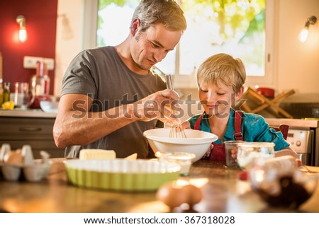 A eight years old blond boy is cooking  with his father in a luminous kitchen. They are sitting at a wooden table the dad is mixing the preparation while his son is adding ingredients.Shot with flare - stock photo