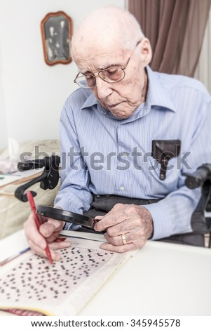 A elderly man sitting doing crosswords hobby - stock photo