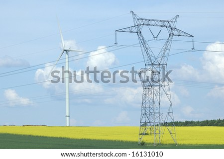 A electric pylon near windturbine over rapeseed field France - stock photo