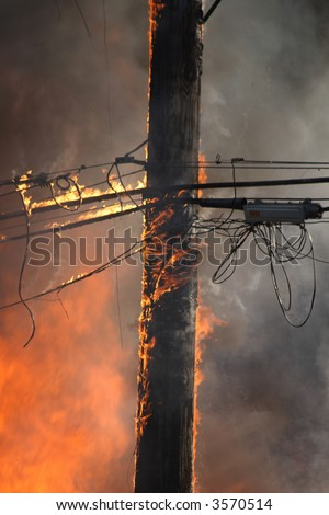 A electrical pole on fire in the midst of a huge blaze - stock photo