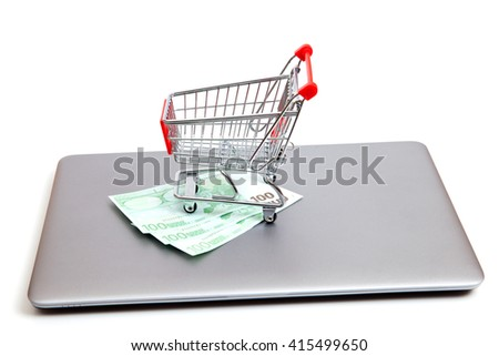 A empty shopping car is standing on notebook and three hundred euros