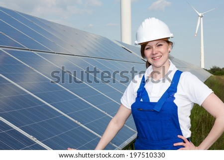 A engineer or installer posing with solar panels - stock photo
