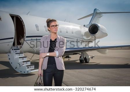 A executive business woman leaving a plane - stock photo