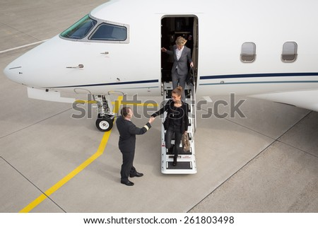 A executive business woman leaving a plane handshake with pilot - stock photo