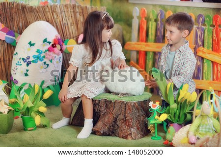 a fabulous farm boy and girl playing with white rabbit - stock photo