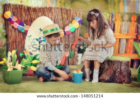 a fabulous farm with yellow tulips boy and girl playing with a carrot - stock photo