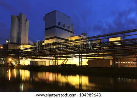 A factory near a river by night.