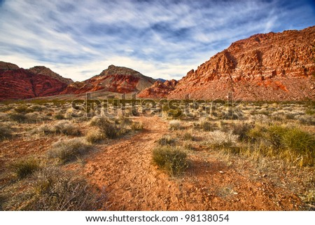 A faint dirt trail leads into the wilderness of Red Rocks Canyon State Park outside of Las Vegas, Nevada. - stock photo