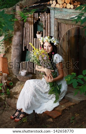 a fairy girl sitting near the forest house of dwarfs - stock photo