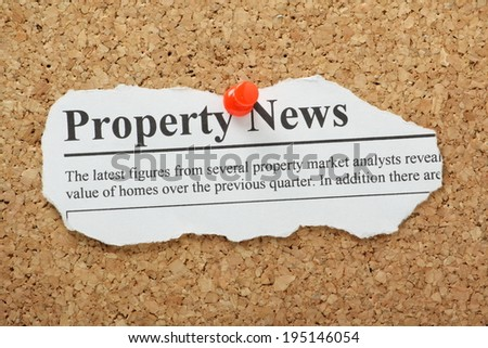 A fake Property News headline torn out and pinned to a cork notice board - stock photo