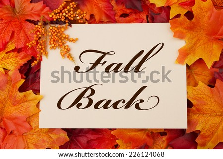 A Fall Back card, A beige card with words Fall Back over red and orange maple leaf background - stock photo