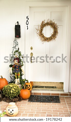 A Fall door adorned with a wreath and surrounded by pumpkins, pinecones and jack-o-laterns. - stock photo
