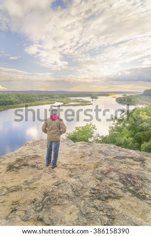 A fall hiker watches the sun going down - stock photo