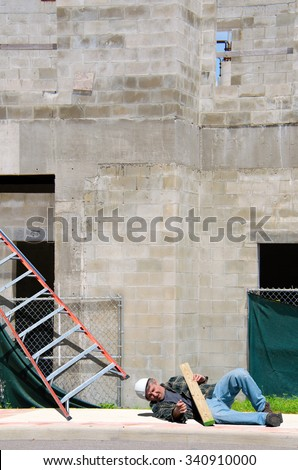 A fallen injured construction worker in a hard hat laying on the ground at the foot of a ladder on a construction work site - stock photo