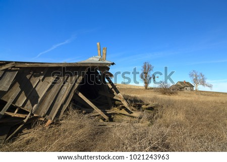 A fallen old barn with an abandoned house in eastern Washington.