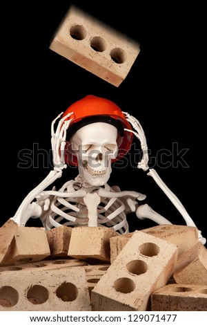A falling brick is about to make contact with a hard hat on the skull of a skeleton.