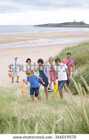 A family are at the beach together, they are all walking up the sand dunes, smiling and talking. - stock photo