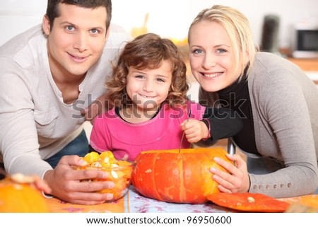 A family carving a pumpkin. - stock photo