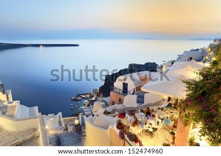 A family enjoying dinner at a restaurant in Santorini. - stock photo