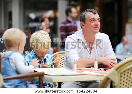 A family, father with teenager son and baby daughter are relaxing in cafe on a summer terrace, waiting for dinner meal, boy is playing with gadget, smart phone - stock photo
