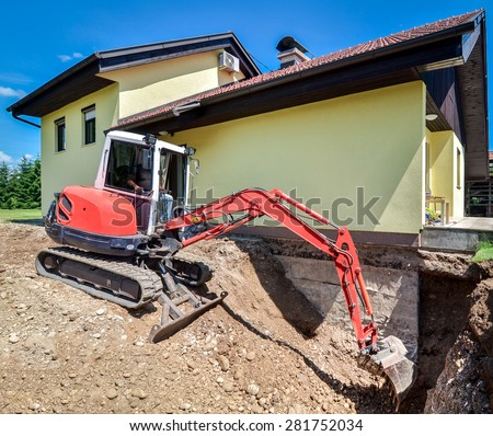 A family house is being rebuilt and renovated with the help of an excavator. Digger is digging dirt and excavating the basement. Digging the brick foundation for hydro isolation  insulation basement. - stock photo