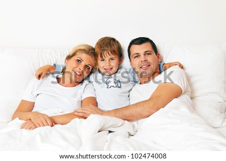 a family is in bed in the morning and having fun - stock photo