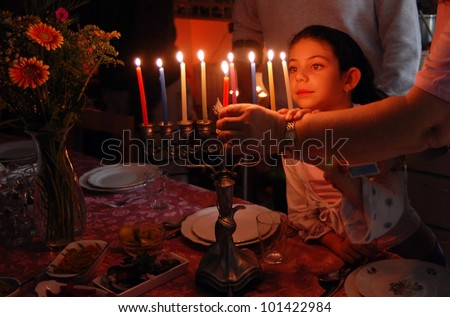 A family is lighting a candle for the Jewish holiday of Hanukkah. - stock photo