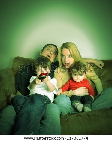 A family is watching television together on a couch and look shocked at what they see. - stock photo