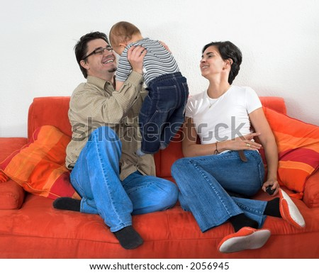 A family of a toddler, a mother and a father are having fun together at home. - stock photo