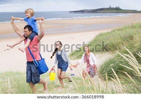A family of four are leaving the beach together. The little boy i on his dads shoulder smiling. - stock photo