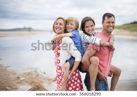 A family of four are on the beach. The parents have the children on their back, they are all smiling looking at the camera. - stock photo