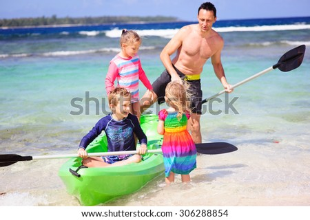 A family of four, dad and his three children enjoying the sunny weather at a tropical beach with a kayak - stock photo