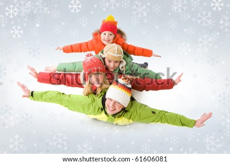 A family of four in warm clothing lying on each other with outstretched arms