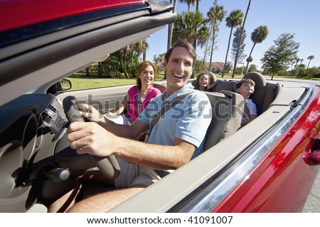 A family of four, mother, father, son and daughter driving in a convertible car on a sunny day in hot location with palm trees - stock photo