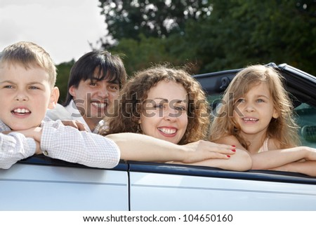 A family of four sits in a open top car, parents smile and look into the camera, children look the other way.