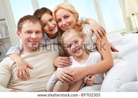 A family of four sitting on sofa, embracing and smiling