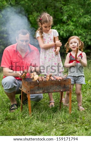 A family of three making barbecue on the grill - stock photo