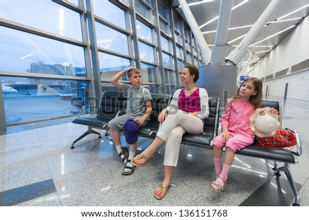A family of three sitting in a recreation area at the airport - stock photo