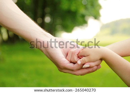 a Family parents hold the hand of a small child