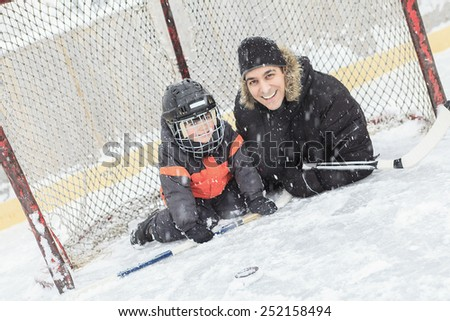 A family playing at the skating rink in winter. - stock photo