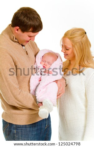 A family portrait of three people in the studio including mother father and newborn baby girl.