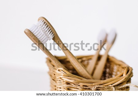 A family set of four wooden bamboo toothbrushes in a straw basket . Two toothbrushes are like parents in love kissing and in focus, and other two - are like children and blurred - stock photo
