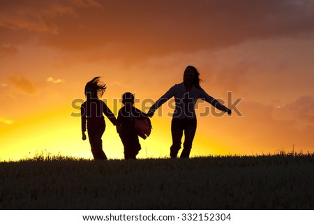 A family skips along happily at sunset. - stock photo