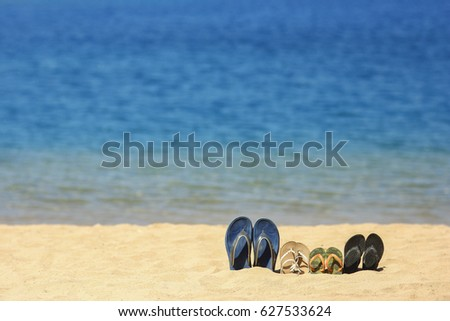 a Family slippers on the sand on the beach